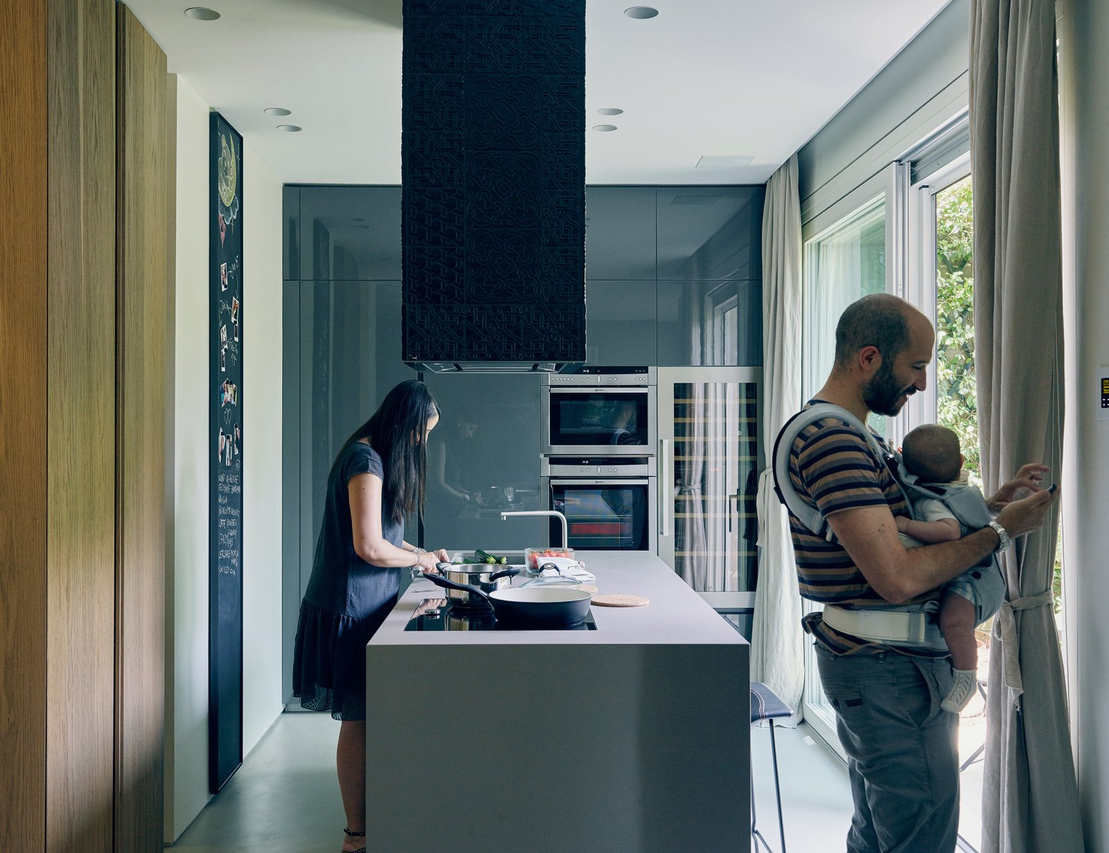 Kitchen, Refrigerator, Wall Oven, Cooktops, Range, Range Hood, Wine Cooler, Ceiling Lighting, Recessed Lighting, and Concrete Floor In remodeling a compact Milan apartment, designers Roberto Di Stefano and Alessandro Bongiorni introduced sliding glass doors by Eclisse where a single door once stood to improve connection to the outdoors. In the brightened kitchen, a Comprex cabinet system pairs with Neff appliances. Domenico Mori tiles cover the range hood.  Photo 2 of 15 in This Growing Family Maximizes Every Last Inch in Their 850-Square-Foot Apartment