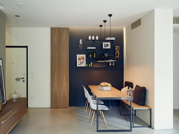 """Sunset pendants by Treviso-based Torremato illuminate a custom table and bench as well as a trio of Eames chairs. Di Stefano and Bongiorno used lighting to structure the open plan: """"We put accents on focus points; we didn't want the light completely spread out,"""" Di Stefano says."""