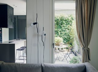This Growing Family Maximizes Every Last Inch in Their 850-Square-Foot Apartment - Photo 8 of 14 - The couple often use the terrace for enjoying an espresso or aperitivo. Parentesi lights by Achille Castiglioni and Pio Manzù for Flos hang next to one of the two entrances to the balcony.
