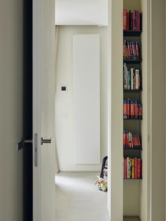 """This Growing Family Maximizes Every Last Inch in Their 850-Square-Foot Apartment - Photo 10 of 14 - The designers sought to create an abundance of storage options—including narrow niches in the hallway, used to hold travel guides. As Di Stefano puts it: """"When a client says, 'I've filled allmy wardrobes and still have space left over,' that means the mission is accomplished."""""""