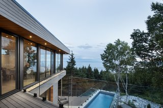 The second floor includes another open plan that blends the kitchen, dining area, and living room together. After ascending to the top, another deck folds over the pool to create an overhang. The wide-spanning glass wraps around the top of the cantilever to take full advantage of the natural setting.