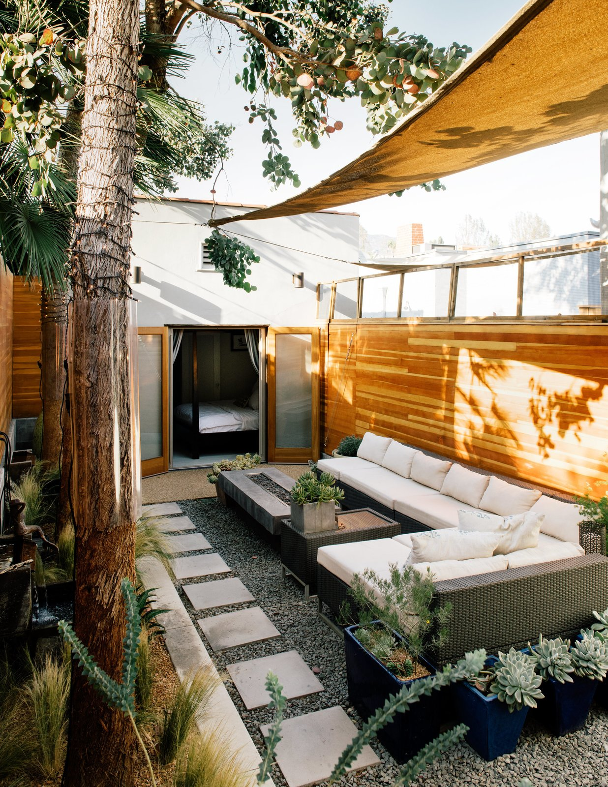 A wicker sectional from Target and a custom fire table that Todd designed sit under Sunbrella shade sails.  Photo 4 of 4 in This Backyard Triumphs Over Trouble to Become an Oasis of Calm