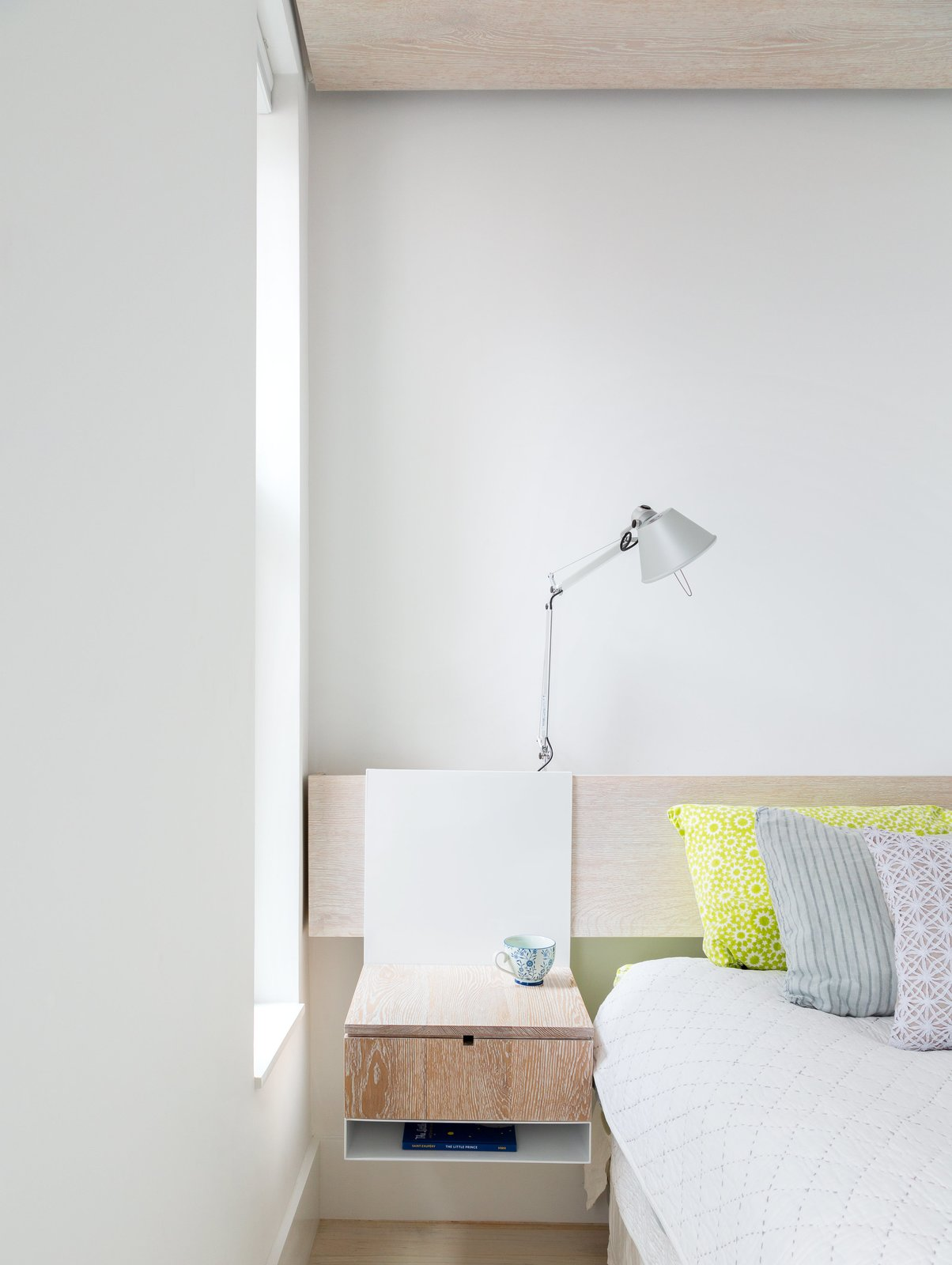 Rather than clutter the master bedroom with furniture, Frame Design Lab created a system where night stands hang from a wall-mounted headboard. Tagged: Bedroom, Bed, Lamps, Night Stands, Shelves, Light Hardwood Floor, Table Lighting, and Wall Lighting.  Photo 2 of 8 in This 60-Square-Foot Structure Divides and Conquers in a Manhattan Renovation