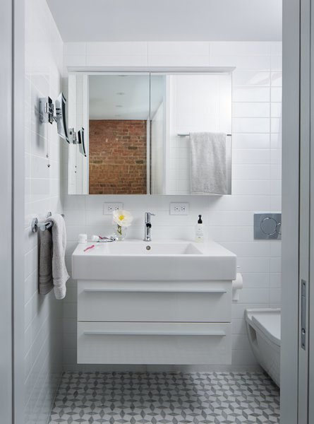 Bath Room, Subway Tile Wall, Drop In Sink, One Piece Toilet, and Ceiling Lighting In the bathroom,a little-used tub was replaced by a streamlined shower. Both the Duravit medicine cabinet and the Kimball & Young makeup mirror feature built-in LED lighting.  Photo 8 of 9 in A 16-Foot-Wide Triplex Is Cleverly Reconfigured to Feel Extra Spacious