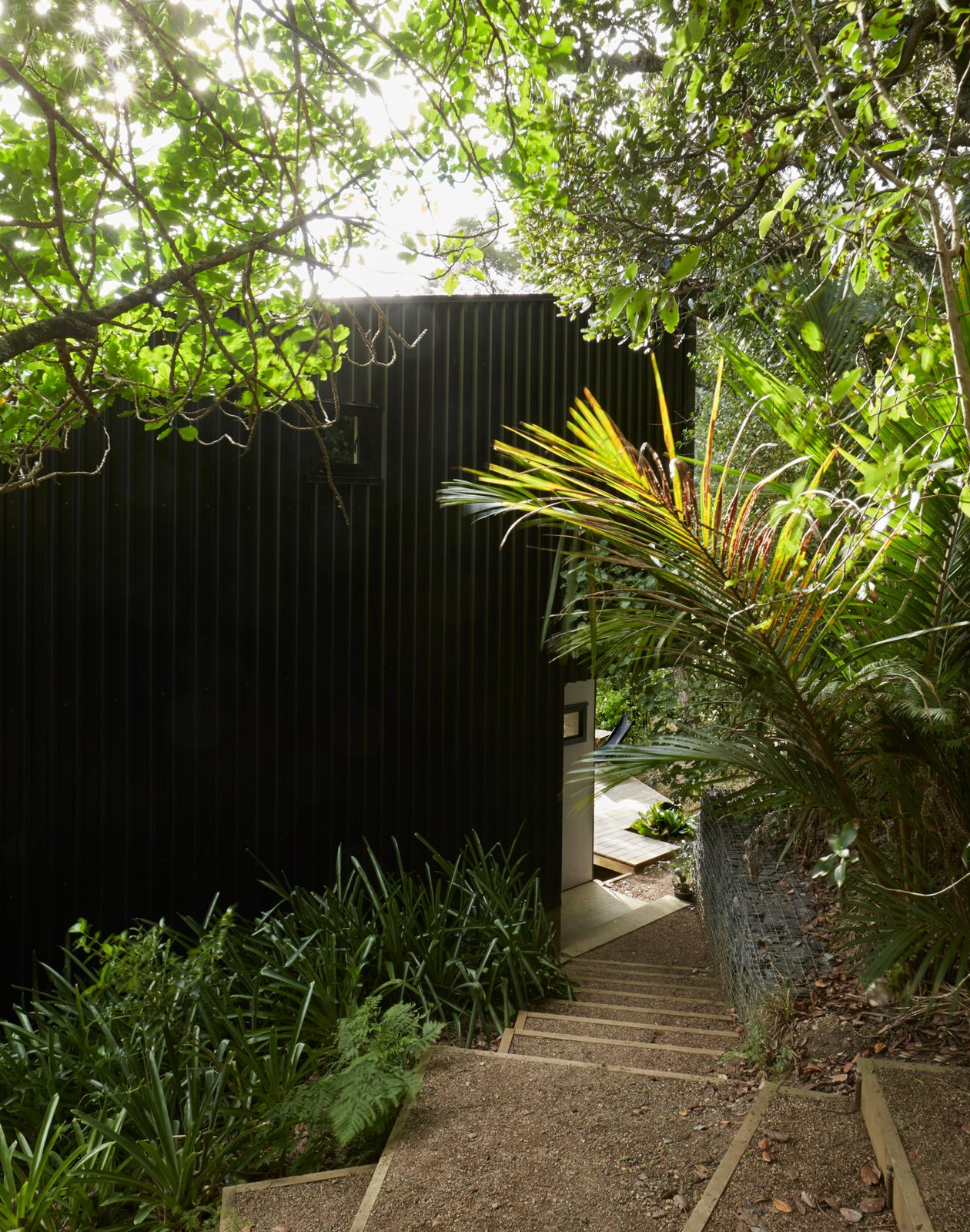 """Seeking a private escape from busy Auckland life, Milton Henry and Mark Summerville purchased an """"unbuildable"""" lot on Waiheke Island and then rehabbed it over 15 years.A clearing in the bush dictated the footprint,resulting in two stacked volumes that form a tower-like structure over four split levels. It took a customized trailer to bring materials to the steep site. Tagged: Exterior, House, and Metal Siding Material.  Photo 2 of 13 in A Tiny Footprint Isn't So Bad When You Live in a Tower"""