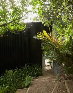 """Seeking a private escape from busy Auckland life, Milton Henry and Mark Summerville purchased an """"unbuildable"""" lot on Waiheke Island and then rehabbed it over 15 years. A clearing in the bush dictated the footprint,resulting in two stacked volumes that form a tower-like structure over four split levels. It took a customized trailer to bring materials to the steep site."""