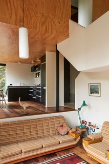 The mezzanine daybed is set in a windowed nook within shelves recycled from a Lundia system. Peta Tearle designed the color scheme and chose the black Melteca kitchen cupboards, which echo the exterior.