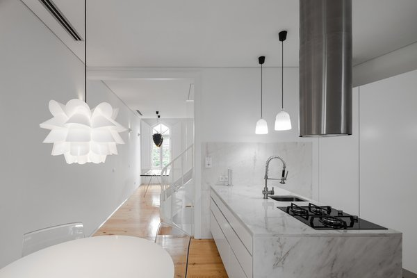 Natural materials are contrasted with white surfaces. After 120 years, this Portuguese building required a little more than just a fresh coat of paint. Tiago do Vale Architects revived the 19th-century dwelling by retaining original details like wooden window frames, the traditional eave, and ceilings while updating the entire structure with a minimalist's touch.
