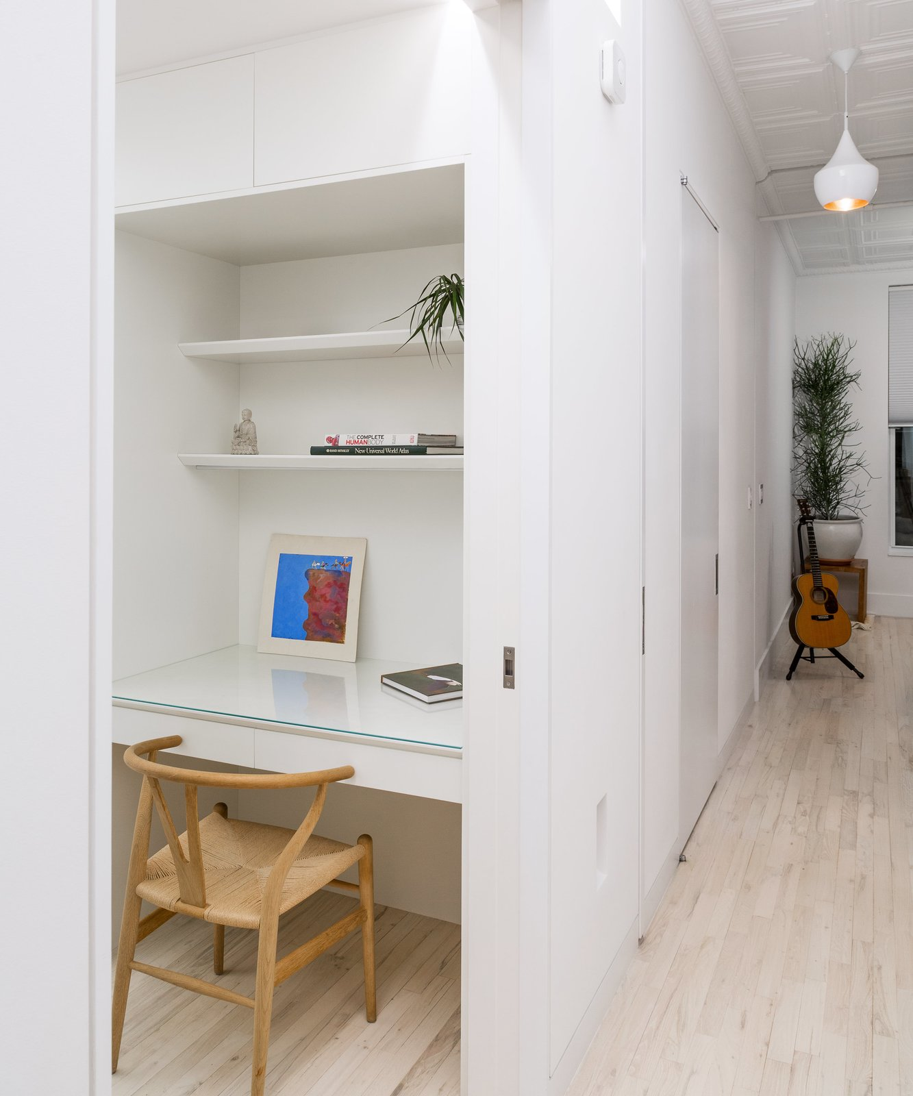 Office, Study Room Type, Bookcase, Shelves, Lamps, Light Hardwood Floor, Chair, Storage, and Desk Inside the Cube, a Wishbone chair by Hans Wegner pulls up to a built-in painted lacquer desk.  Photo 6 of 8 in This 60-Square-Foot Structure Divides and Conquers in a Manhattan Renovation