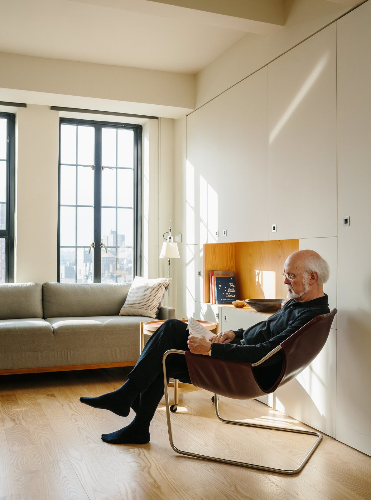 Living Room, Chair, Sofa, End Tables, Storage, Coffee Tables, Shelves, Lamps, Table Lighting, and Light Hardwood Floor Resident Paul Andersson lounges in a Paulistano armchair by Paulo Mendes da Rocha.  Photo 4 of 9 in A Pivoting Wall Makes This Tiny Studio a Fit For Any Occasion
