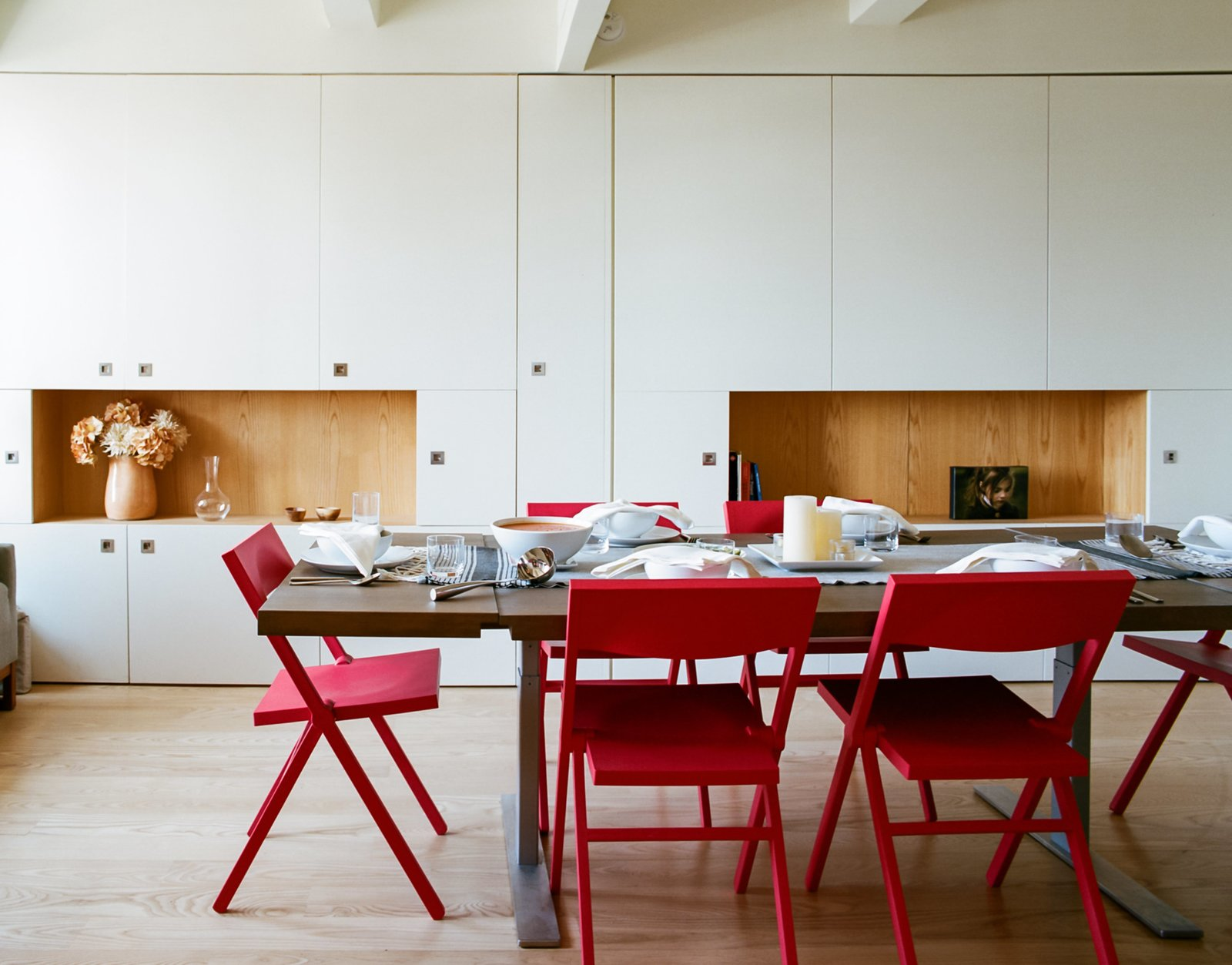 Dining Room, Chair, Table, Storage, Shelves, and Light Hardwood Floor The red Piana folding chairs are by David Chipperfield for Alessi; Garneau custom-designed the millwork tabletop and stainless-steel legs.  Photo 6 of 9 in A Pivoting Wall Makes This Tiny Studio a Fit For Any Occasion