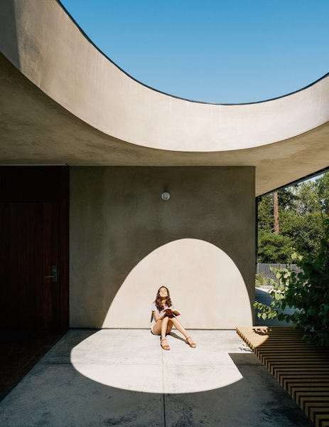 For the breezeway, Schwartz used concrete to achieve the feel of a hardscape courtyard. Uma basks beneath the egg-shaped opening.  Photo 3 of 9 in A Family Guesthouse Made for Accessibility, Aging in Place—and That View