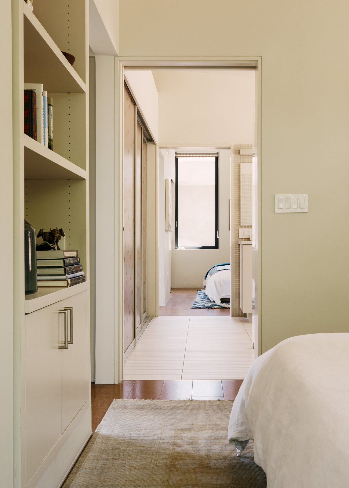 Bedroom, Bed, Shelves, Storage, and Cork Floor In the bathroom, narrow porcelain floor tiles, which require more grout, provide extra traction to prevent slips.  Photo 7 of 9 in A Family Guesthouse Made for Accessibility, Aging in Place—and That View