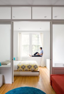 By replacing a wall with a custom wood-and-glass partition, architect Matt Krajewski transformed a previously dark one-bedroom railroad apartment in Manhattan into a light-filled home. Compact furnishings, like a Mandal bed frame from IKEA with integrated storage, maximize every inch of the 390-square-foot unit, which is housed in a former tenement building.