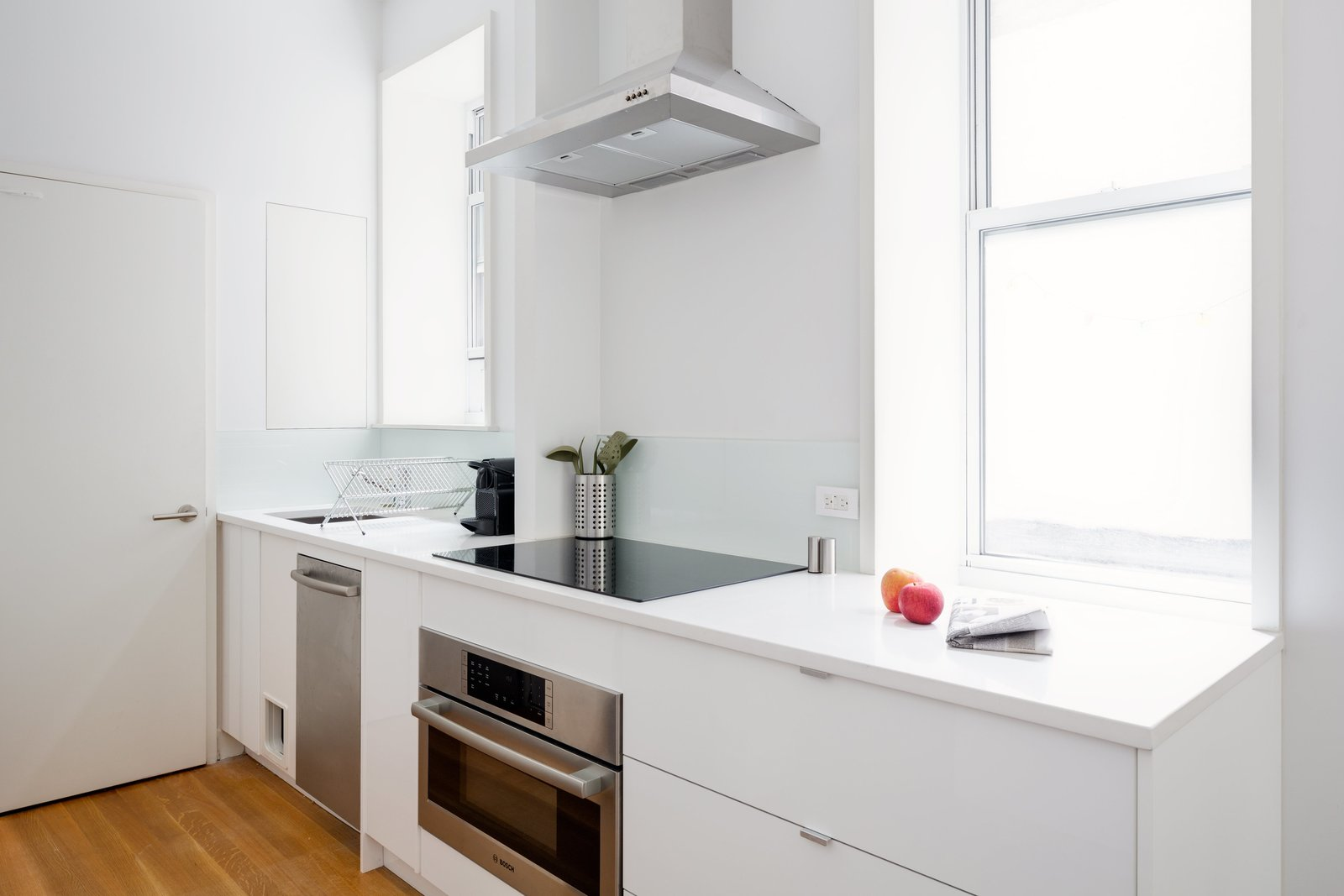 Kitchen, Cooktops, Range Hood, Range, Dishwasher, White Cabinet, Undermount Sink, and Medium Hardwood Floor The space-saving appliances are all from Bosch's 500 and 800 series.  Photo 6 of 10 in This 390-Square-Foot Renovation Is Compact Yet Comfortable in Greenwich Village