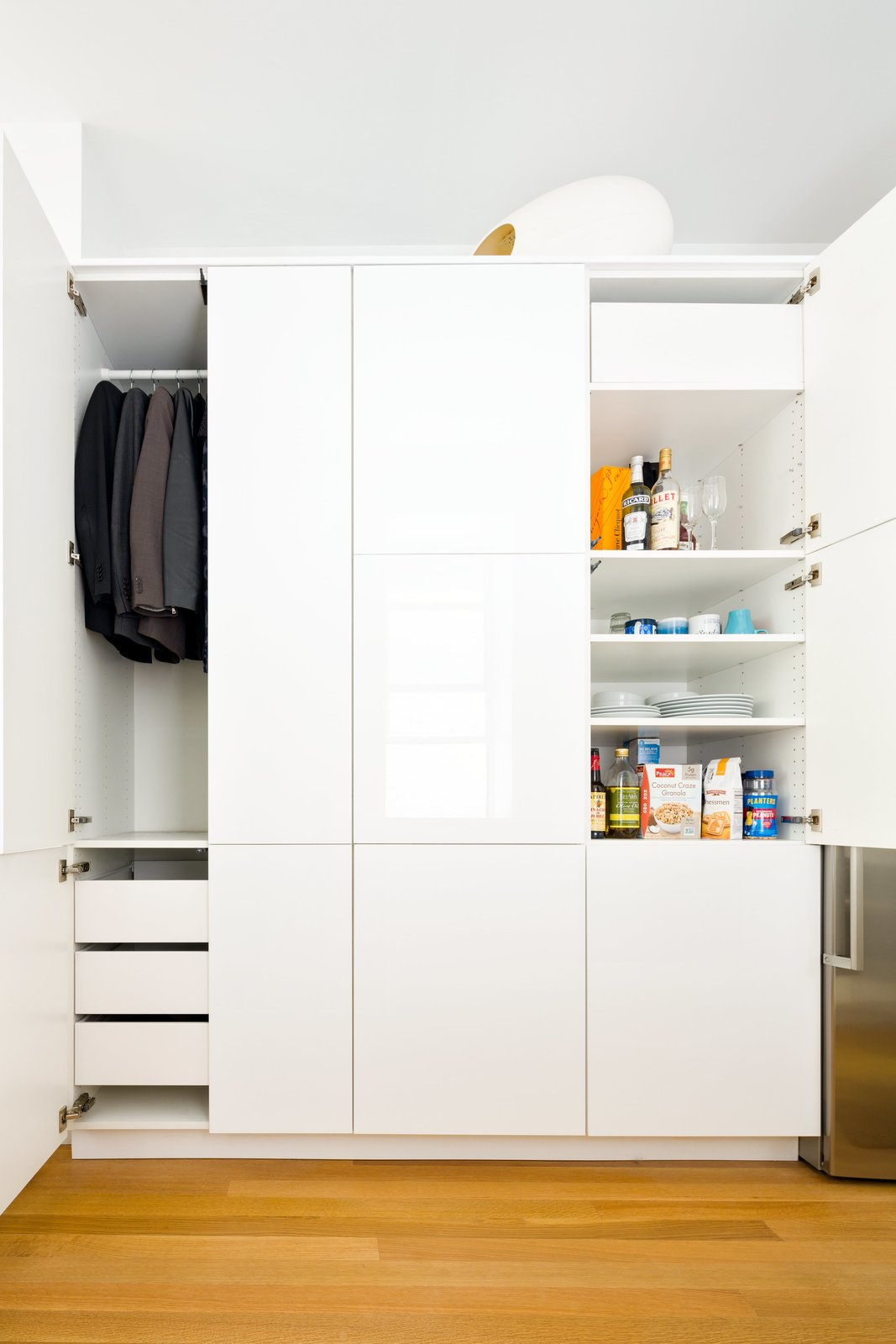 In the kitchen, a single Sektion wardrobe from IKEA is used to stow both clothing and various food and dining items. Throughout the apartment, Krajewski replaced the time-worn flooring, installing new white oak planks by Hull Forest with a buffed oil finish by Waterlox. Tagged: Storage Room, Closet Storage Type, Cabinet Storage Type, and Shelves Storage Type.  Photo 8 of 10 in This 390-Square-Foot Renovation Is Compact Yet Comfortable in Greenwich Village