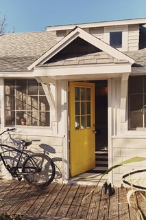 The door to the front porch, painted in Bright Yellow by Benjamin Moore, is inspired by the island's local flora.