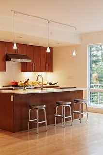Presented with three possible kitchen units by Blu Homes, the residents selected one that has less cabinetry and a more fluid layout. The bar stools are from Crate and Barrel.