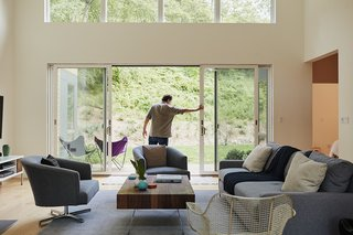 In the living room, a 16-foot-wide sliding glass door opens onto a landscape designed by Rosedale Nurseries.