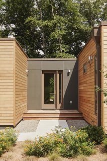 The mudroom is the project's most customized component. Built on-site, it connects the house with two other Blu Homes prefab designs: an Origin studio, containing the gym/office, and a W-Series garage. James Hardie Reveal siding in Iron Gray distinguishes it from the factory-built modules, which are clad in Western red cedar.