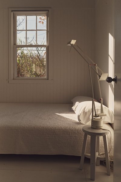 The all-white guest bedroom features a West Elm bed, covers by Garnet Hill, and a Tizio desk lamp by Richard Sapper for Artemide