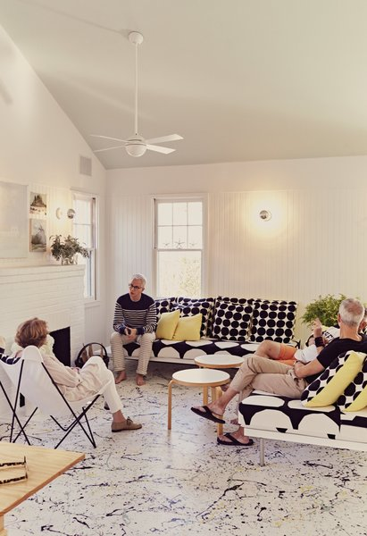 Residents Ann and Tony Spagnola sit with their architects, Peter Stamberg and Paul Aferiat, in front of the whitewashed brick fireplace in the living room. A vintage Butterfly chair joins custom sofas designed by the architects. Coffee tables by Alvar Aalto for Artek and pillows by Marimekko create a clean, Finnish-inflected environment.