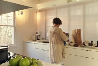 .In the galley-style kitchen, Ann sorts groceries into Akurum cabinets from IKEA. For the sconces, the architects selected generic porcelain sockets, then stylized them with silver-cap bulbs.