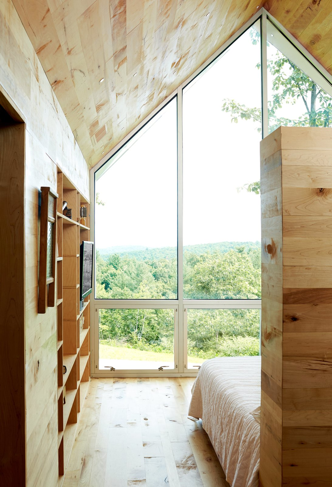Bedroom, Bed, Storage, Bookcase, and Medium Hardwood Floor An 800-square-foot addition expands the Virginia home of Lauren and Josh Stegall. Built for $120,000, the structure has a large window overlooking the Blue Ridge Parkway and Sugarloaf Mountain.  Photo 2 of 8 in Happy Trails