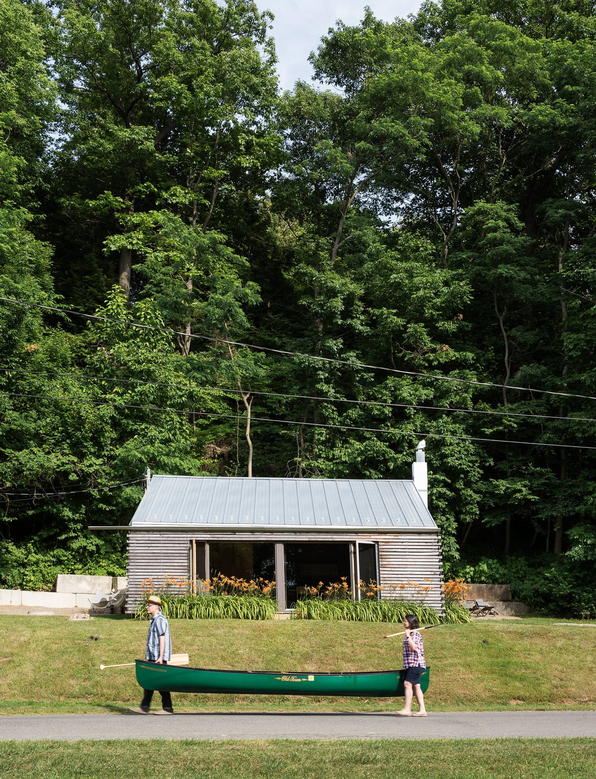 Architects Gerard Damiani and Debbie Battistone turned a budget buy into a condensed cabin getaway. Tagged: Exterior, House, Metal Roof Material, Wood Siding Material, and Gable RoofLine.  Photo 2 of 8 in Cottage Industrious