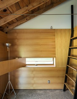 Cottage Industrious - Photo 5 of 10 - A custom ladder made of bent steel with oak treads leads to the sleeping loft, while a white oak panel swings opens to reveal an inset window. Longtime collaborator Jeffrey Kramer crafted the home's wood elements.