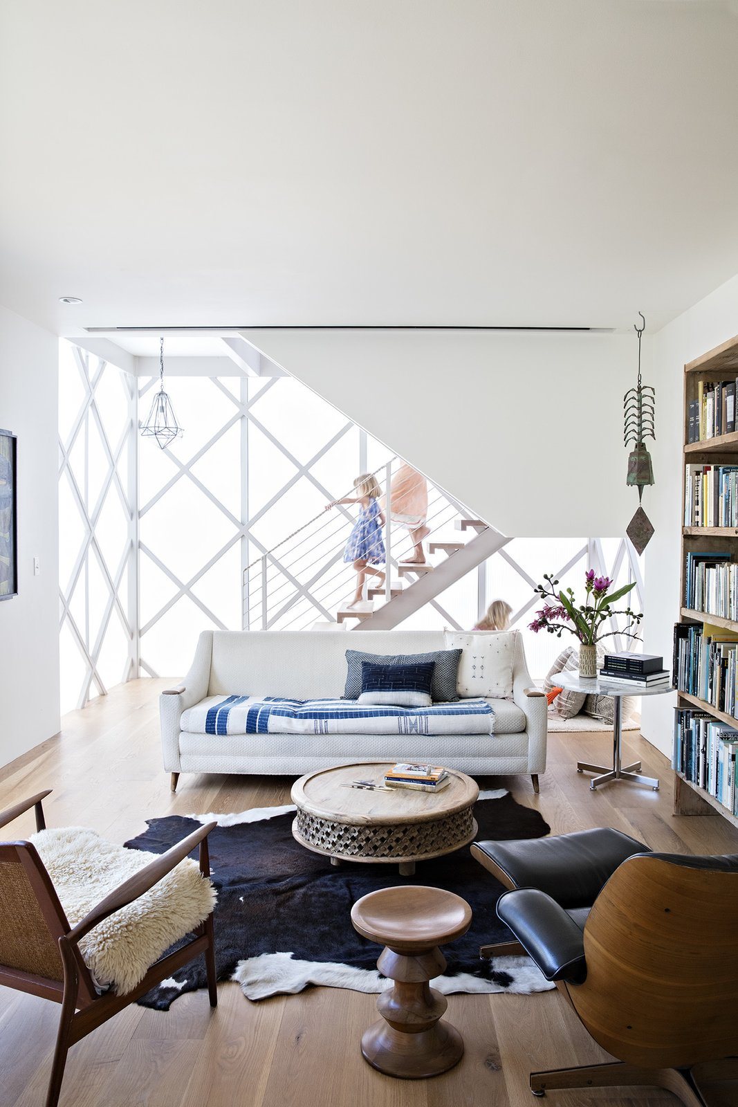 Living Room, Chair, Sofa, Coffee Tables, End Tables, Ceiling Lighting, Pendant Lighting, Medium Hardwood Floor, and Rug Floor Vintage pieces furnish the library, which occupies the ground floor of the modular addition.  Photo 3 of 14 in Such Great Heights