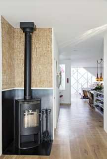 Upcycled Kirei wall board pairs with a Rais Gabo stove in the original part of the house, which connects seamlessly <br>to the prefab addition.
