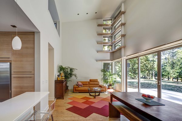 "Four rows of narrow ""light shelves,"" a stylistic signature of Stillwater Dwellings, wrap around a corner wall in the double-height living room. A modular carpet by FLOR covers eucalyptus planks from Cali Bamboo. The leather Violino sofa was purchased at an overstock warehouse.  Photo 3 of 5 in Remote Control"