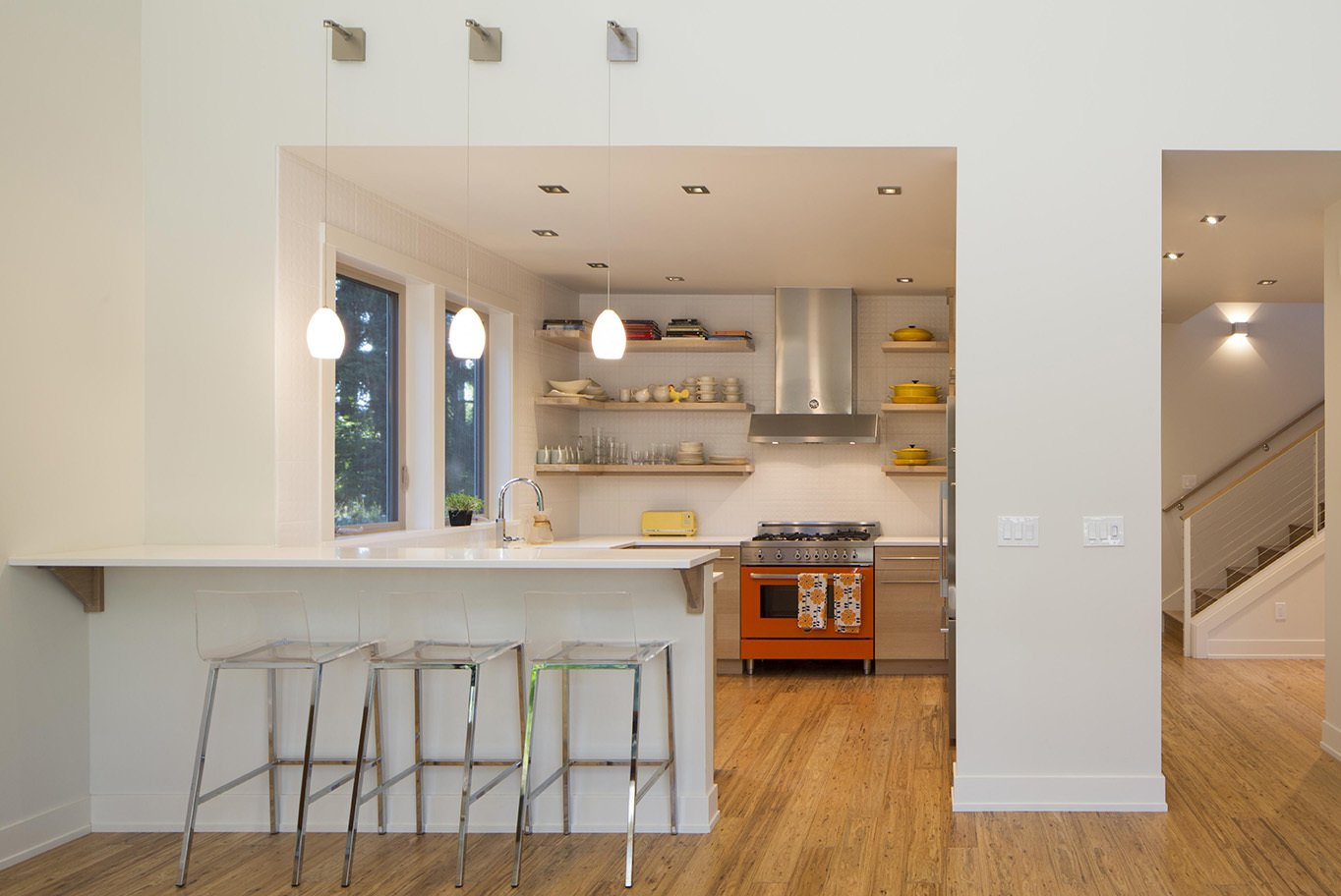 Kitchen, Range, Range Hood, White Cabinet, Light Hardwood Floor, Ceiling Lighting, Recessed Lighting, and Pendant Lighting For the open kitchen, Peter, a former chef, ordered a colorful Bertazzoni range through a showroom in Portland, then decorated the rest of the space around it. The fixture contrasts with the neutral walls, which are painted in Rodda's Dove White.  Photo 5 of 5 in Remote Control