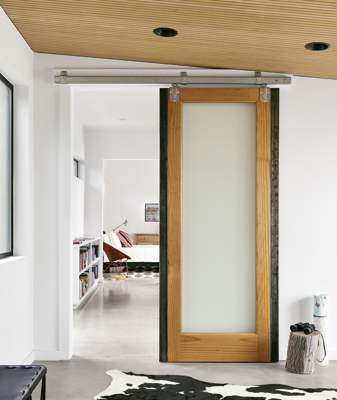 Pops of color and warm materials, like the sliding wooden barn doors from Simpson, provide a cozy contrast to the polished concrete floors throughout.  Photo 2 of 6 in The Long Way Home