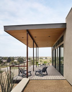 The east-facing facade opens to an outdoor deck, which is furnished with lounge chairs by Loll Designs.