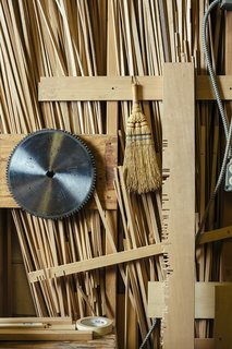 The saw blade, whisk broom, and aligning board that the craftsmen use to create screens hang on a shop wall.