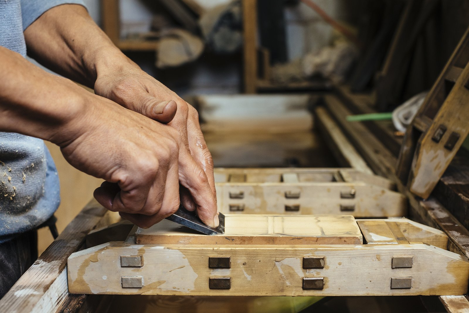 Using a Japanese handsaw, the woodworker, in just one stroke, cuts a channel into the wood,  creating a slot for the rice paper.  Photo 6 of 9 in How to Shape a Shoji, Step by Step