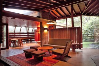 Built with redwood, glass, red brick, and concrete, the house was originally designed by John Lautner for the Schaffer family, who used to spend time enjoying picnics under the resident oak trees. Lautner built the house horizontally around the oaks.