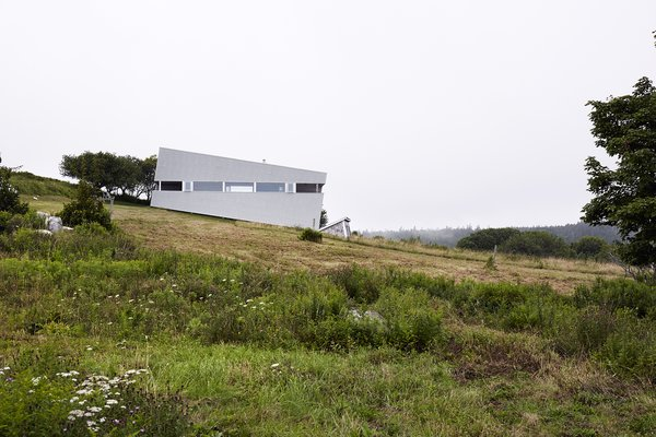 Side Yard, Exterior, Slope, Field, Metal Siding Material, and House Building Type Imagined as a jewel box on a hill, Sliding House takes the place of a barn that once stood on this Nova Scotia site. Its form follows the slope of the land, while the windows are parallel with the horizon, setting up a tension between a plumb interior and a slanted exterior. The tilt of the structure isn't just a visual trick—it also helps the roof to drain. When the distinctive windows are lit from within, the house serves as a beacon for local sailors.  Photo 2 of 13 in Lights Will Guide You Home