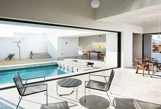 Comprised of stark whitewashed angles and box forms, the interconnected interior is focused around the pool and open walls in order to allow for seamless indoor/outdoor living.