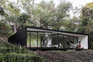 Constructed of steel, glass, and concrete, the exterior is clad in a dramatic black shade with a floor-to-ceiling glass facade—offering views of the valley below from the outdoor lounge area and pool.