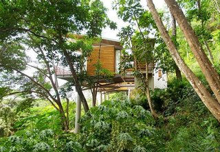 The interconnecting teak-and-bamboo, pod-like design floats above the trees with 180-degree views of the mountains and the Pacific.