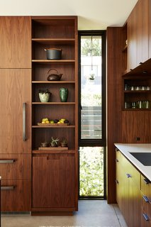 In the kitchen, an elongated window breaks the custom walnut cabinetry by Contour Woodworks.