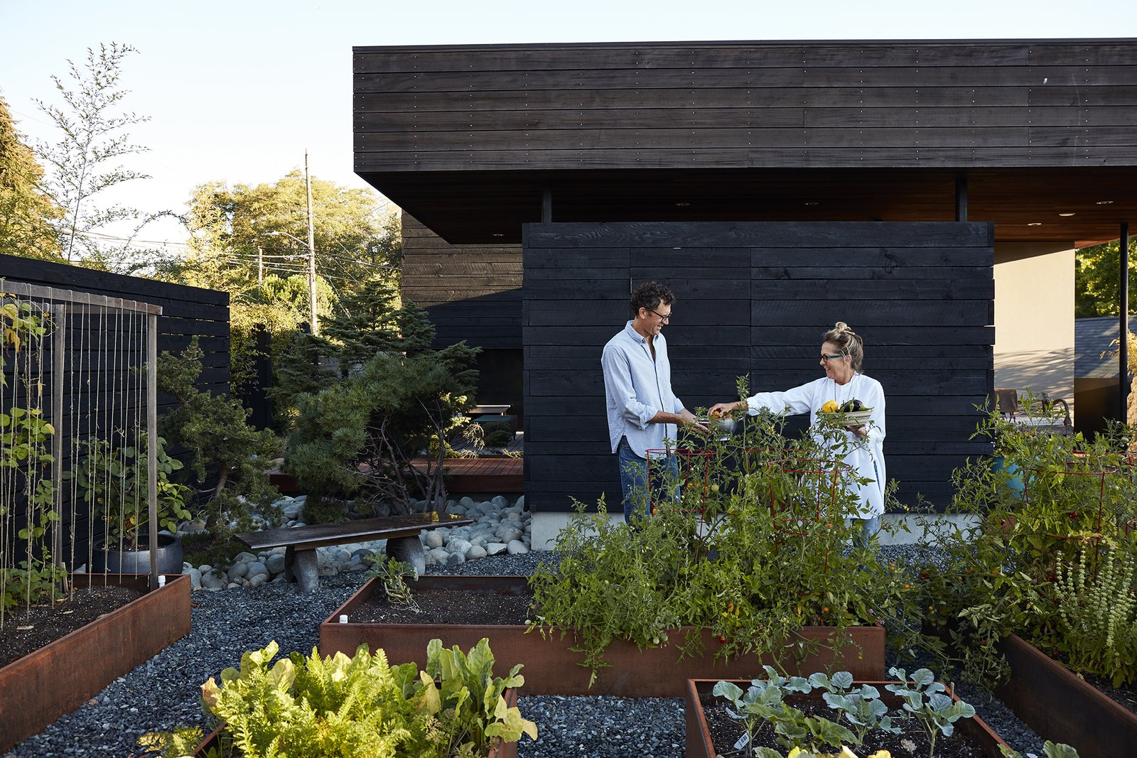Outdoor, Gardens, Stone Patio, Porch, Deck, Planters Patio, Porch, Deck, Garden, Vegetables, Wood Fences, Wall, and Horizontal Fences, Wall Cor-Ten steel planters host a bounty of fresh herbs, fruits, and vegetables.  Photo 14 of 15 in Greener Grass