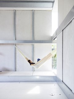 Resident Débora Mesa Molina, an architect and research scientist, lounges in a hammock in the living area of the steel-and-foam prefab addition she and her husband, Anton Garcia-Abril, designed in Madrid, Spain, and assembled in nine days in Brookline, Massachusetts.