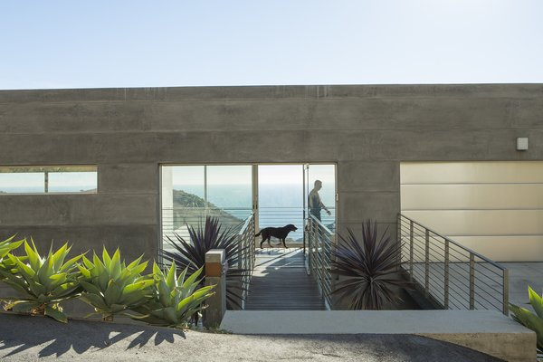 """Simple rectangular  volumes with simple details"" is how designer Thomas Egidi describes the house he created for architect Carlos Dell'Acqua in Malibu. ""I wanted to stress its horizontality,"" Dell'Acqua notes. Inside the dwelling, which is entered via a bridge that pierces the 25-foot-high main facade, the view  opens up to a panorama of mountains and sea. Ipe flooring is used for the walkway and throughout the interior.  Photo 1 of 5 in Facing the Elements"