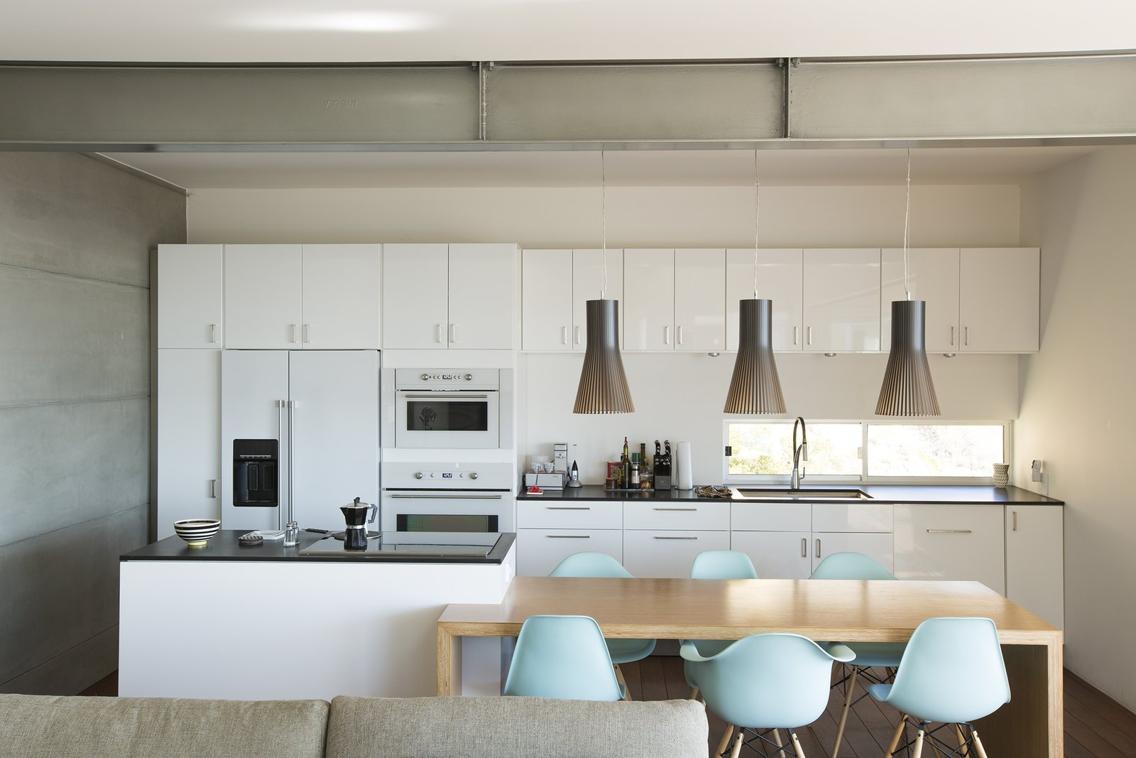Pendants from Finnish Design Shop light a table by carpenter Leo LaPlante. The Eames chairs are from Design Within Reach.  Photo 3 of 5 in Facing the Elements
