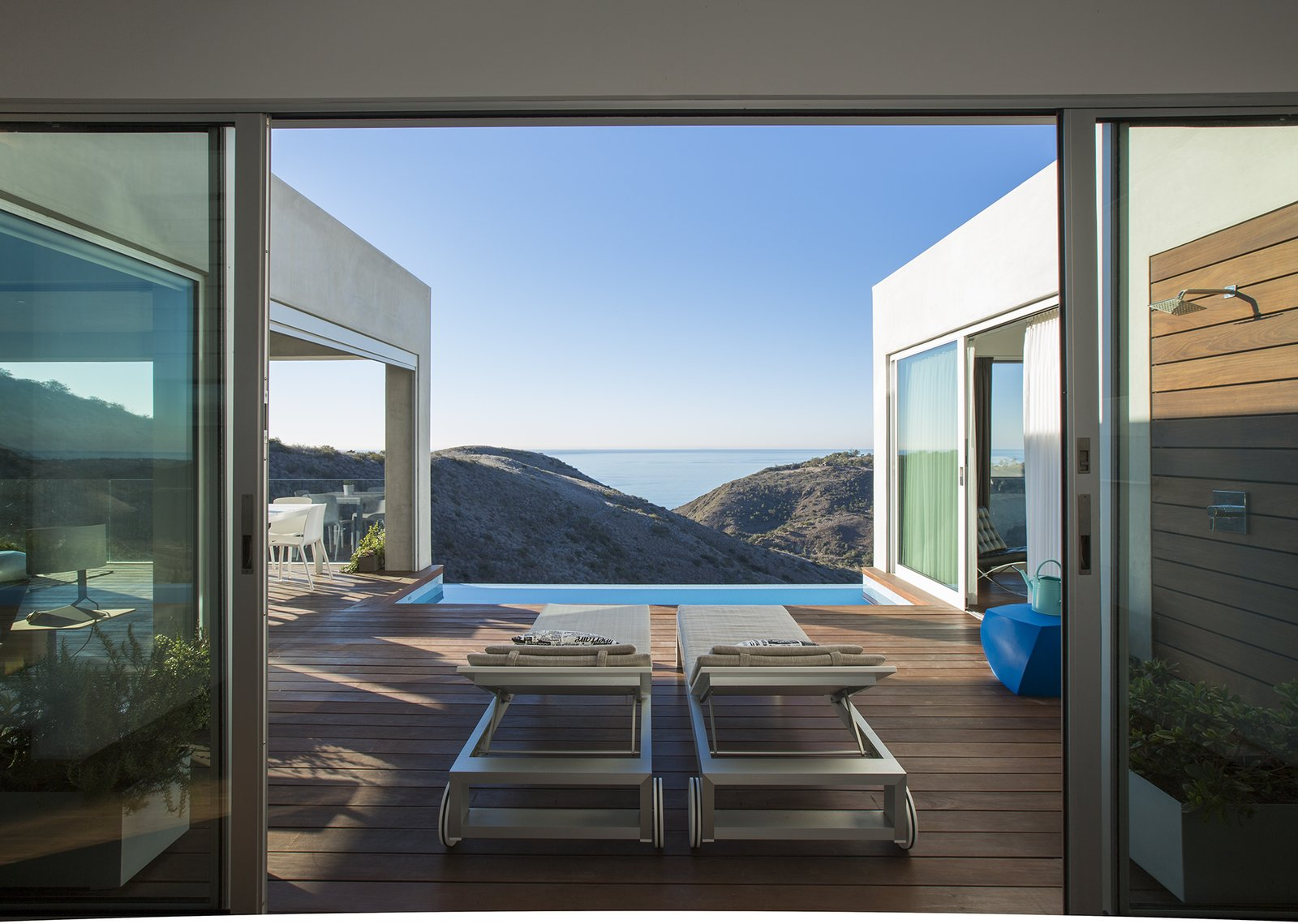 """Lounge chairs by B&B Italia on the lower-level terrace offer a spot from which to take in the ocean views. Of the outdoor shower, Dell'Acqua says, """"It's the most used thing in the house—even in the middle of winter.""""  Photo 5 of 5 in Facing the Elements"""