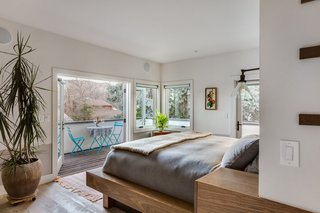 "The master suite is a large space anchored by a custom-built ""island"" that holds the bed on one end and bathroom vanity on the other (see next slide).<br><br>""Since we didn't want to push the whole house out to open up more space, I added a deck instead of altering the footprint,"" says Juilland. The result, he says, is a cozy bedroom that doesn't feel confined."
